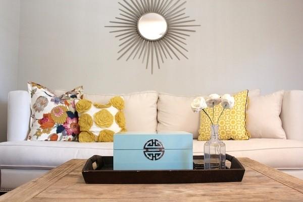 Des coussins avec des motifs floraux et simples sur un canapé beige
