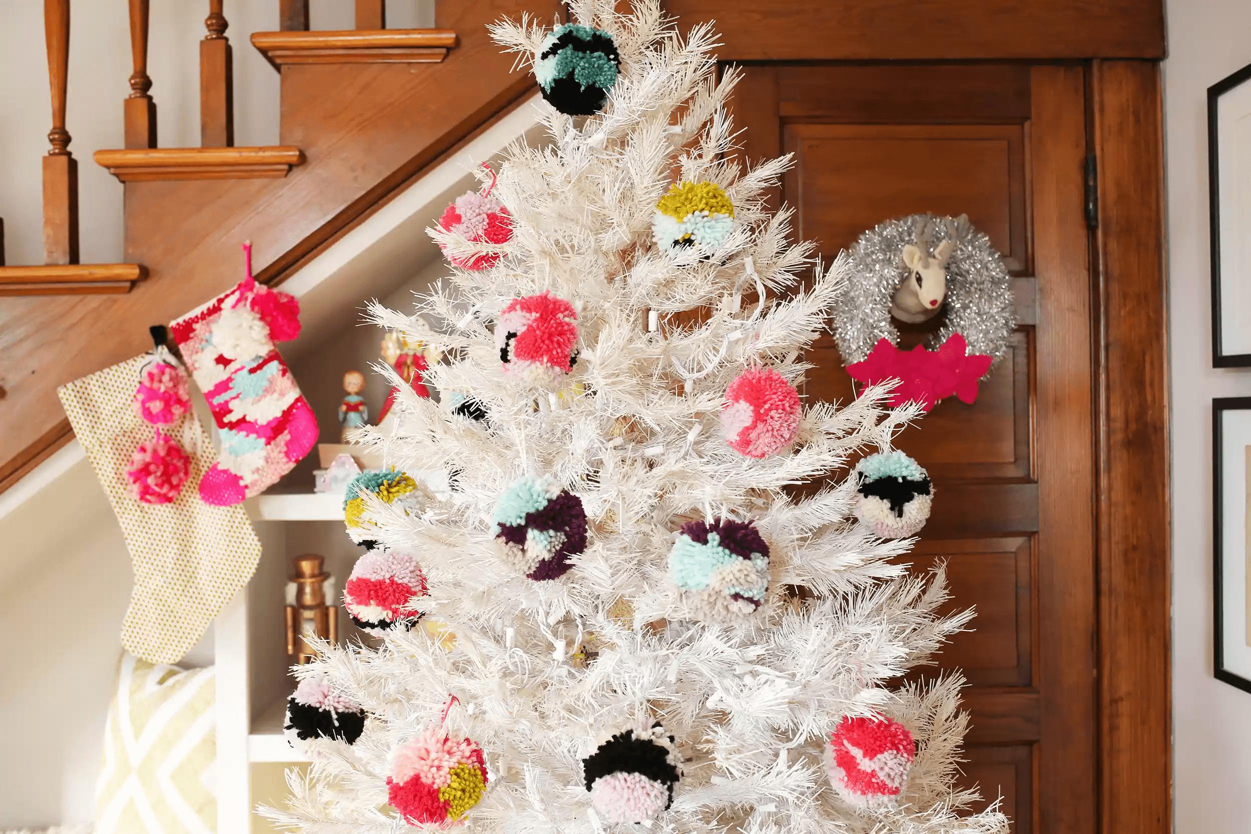 Arbre de Noël blanc avec des décorations de pom-pom girls près d'un escalier en bois