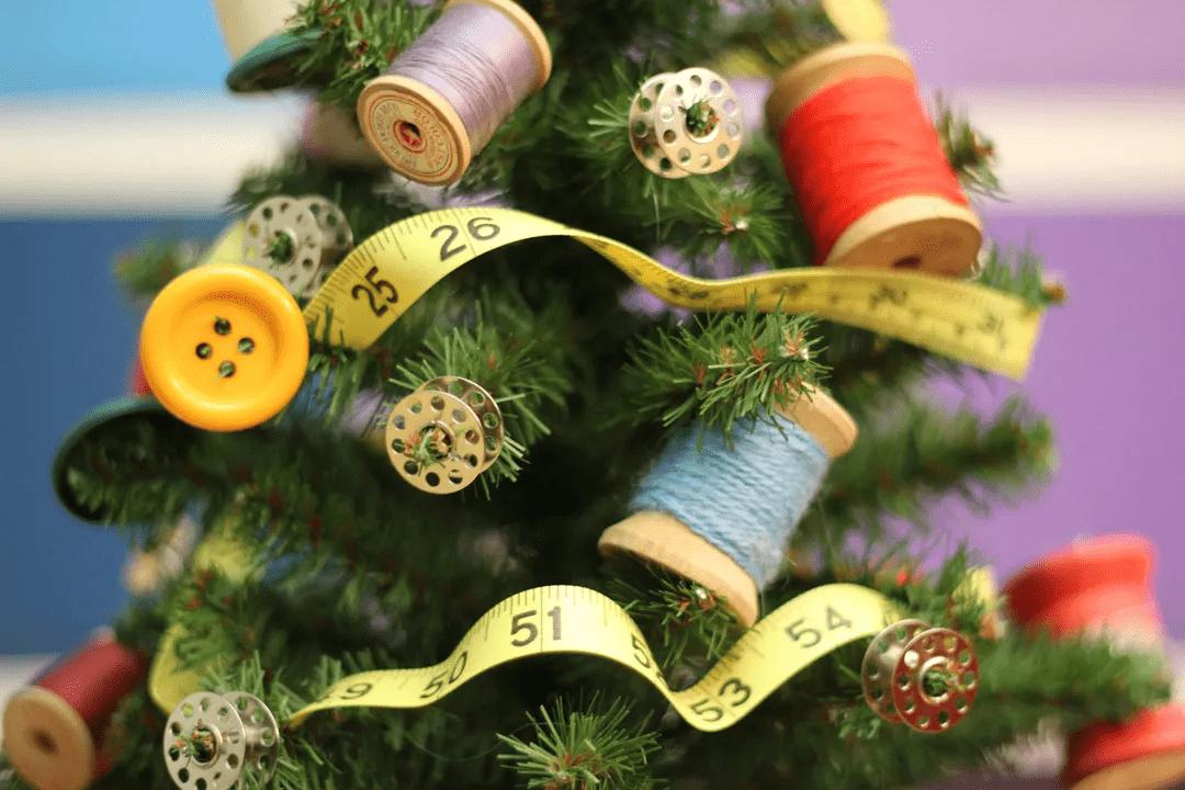 Arbre de Noël orné de fournitures de couture, dont des bobines, des boutons, du fil et du ruban à mesurer