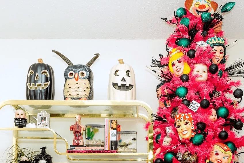 Un sapin de Noël rose orienté vers Halloween avec des masques et des décorations noires