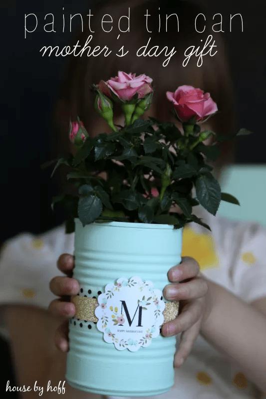 Boîte de conserve peinte avec ruban et emblème M tenant des roses