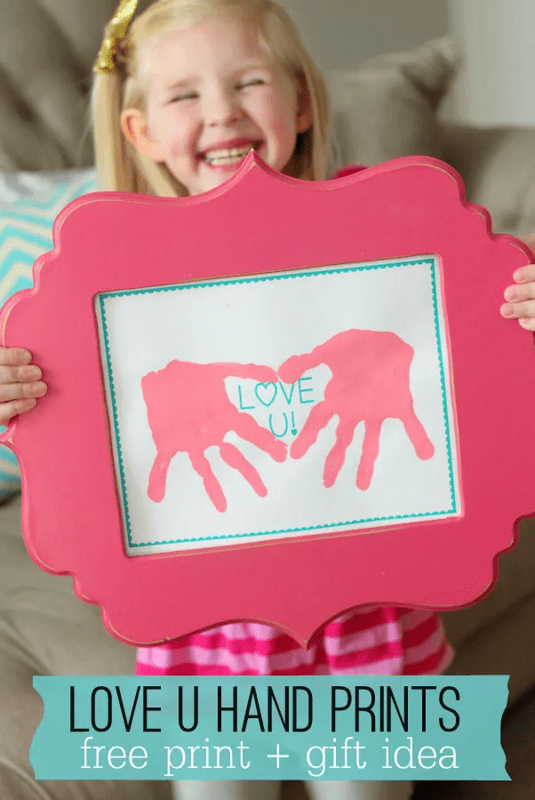 Fille tenant une empreinte de cœur dans un cadre rose